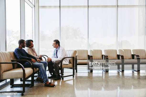 doctor discussing with family while sitting hospital waiting room - healthcare stock pictures, royalty-free photos & images