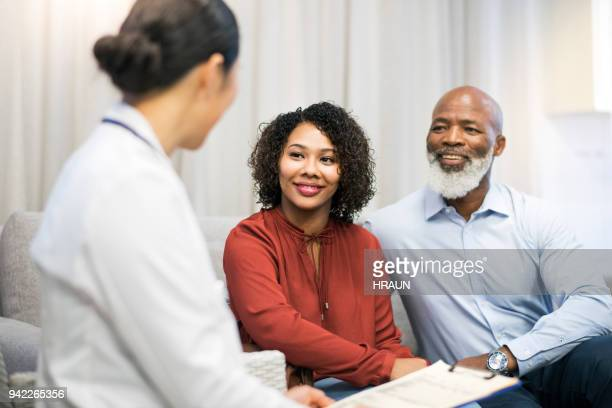 doctor discussing with patient on sofa in clinic - visita imagens e fotografias de stock