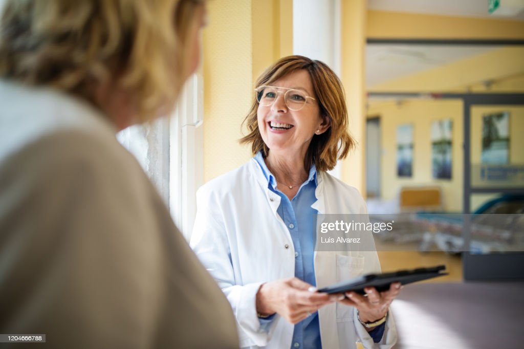 Doctor discussing with woman at nursing home : Stockfoto