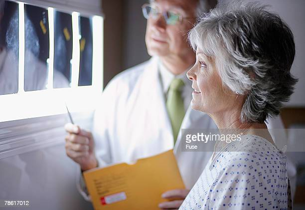 doctor discussing x-rays with middle aged woman - mammogram stock pictures, royalty-free photos & images