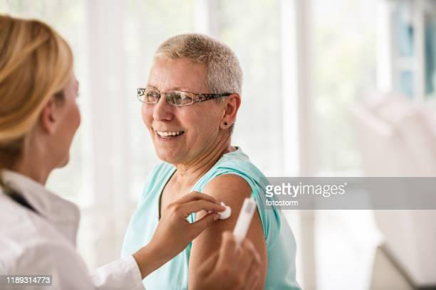 doctor disinfecting patient's arm before vaccination - vaccination stock pictures, royalty-free photos & images