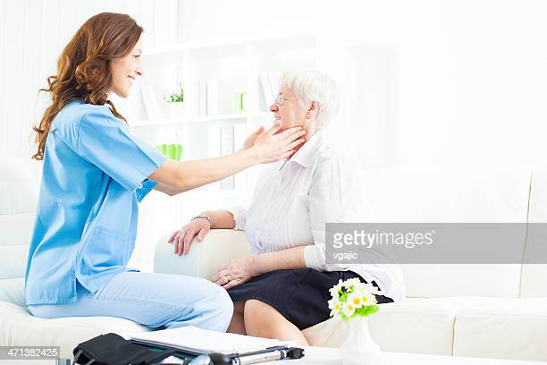 doctor doing glands exam to senior woman. - thyroid gland stock pictures, royalty-free photos & images