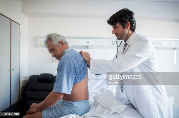 Doctor doing his medical rounds at the hospital listening to a patients lungs