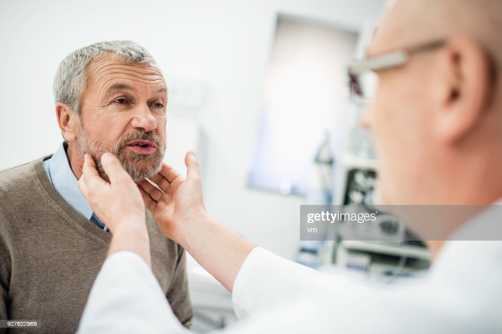Doctor doing throat examination on older caucasian man : Stock Photo