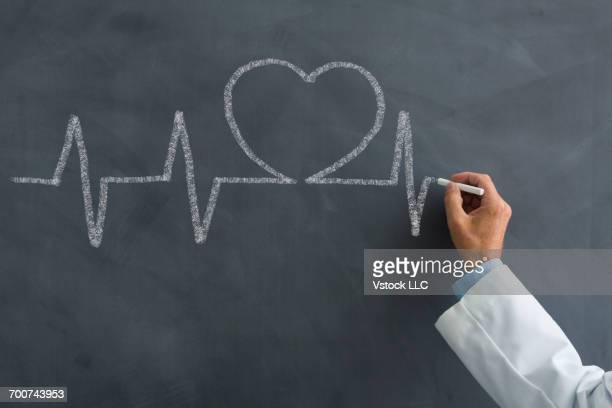 Doctor drawing pulse trace and heart on blackboard