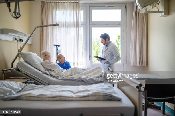 doctor during a routine check up of a senior patient - hospital ward stock pictures, royalty-free photos & images