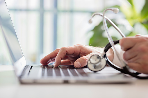 Doctor entering patient notes on laptop in surgery 924365076