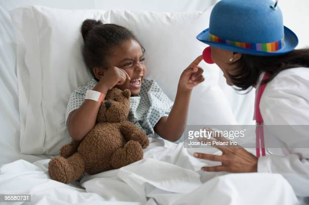 doctor entertaining girl in hospital bed - clown stock-fotos und bilder