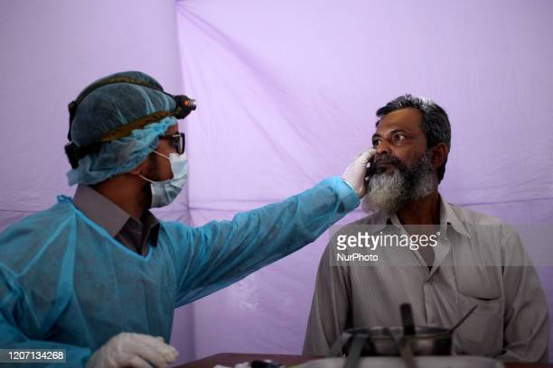 Doctor examines an elderly patient at a temporary medical camp inside Dhaka Medical College Hospital compound amid the corona virus epidemic in...