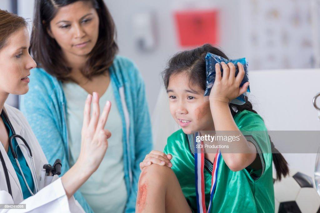ER doctor examines dazed injured soccer player : Stock Photo