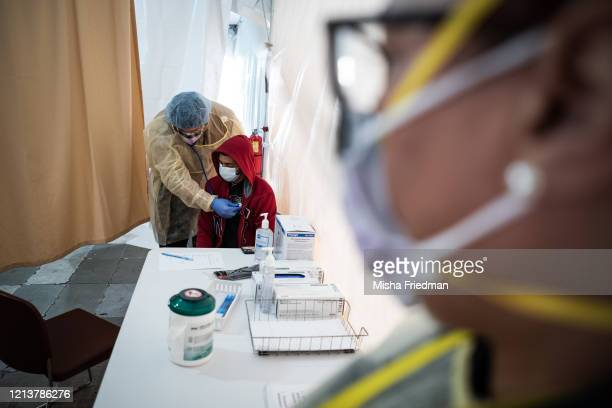 A doctor examines Juan Vasquez for a COVID19 test inside a testing tent at St Barnabas hospital on March 20 2020 in New York City St Barnabas...