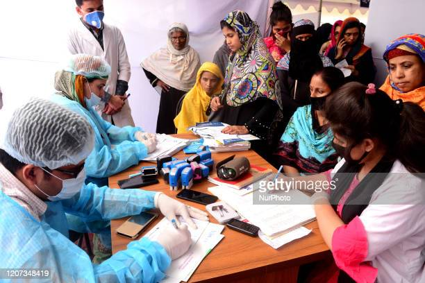 Doctor examines patients at a temporary medical camp inside Dhaka Medical College Hospital compound amid the corona virus epidemic in Dhaka,...