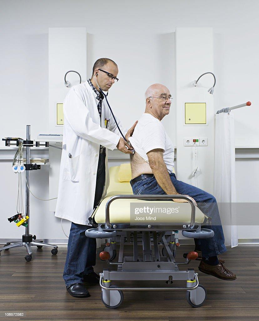 doctor examing senior man with stethoscope : Stock Photo