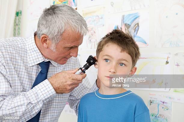Doctor examining a boy's ear