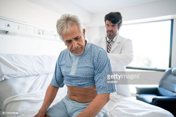 Doctor examining a hospitalized senior patient checking his lungs