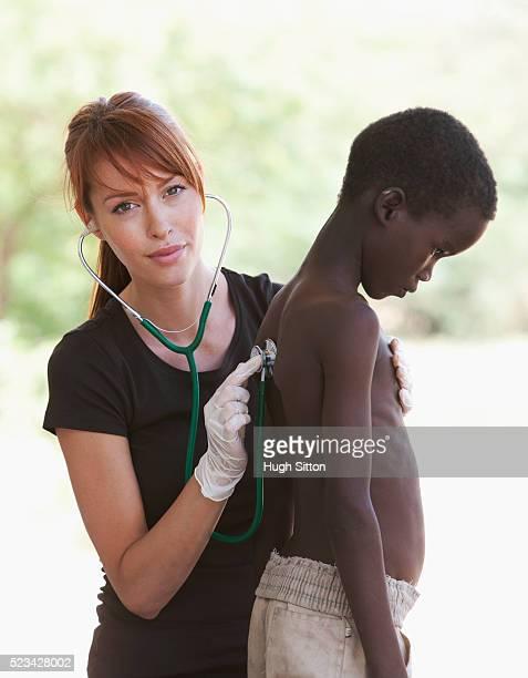 doctor examining a young boy, kenya - hugh sitton bildbanksfoton och bilder
