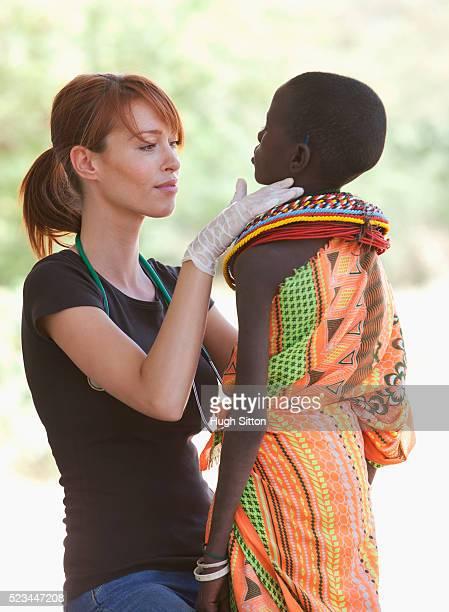 doctor examining a young samburu girl, kenya - hugh sitton imagens e fotografias de stock