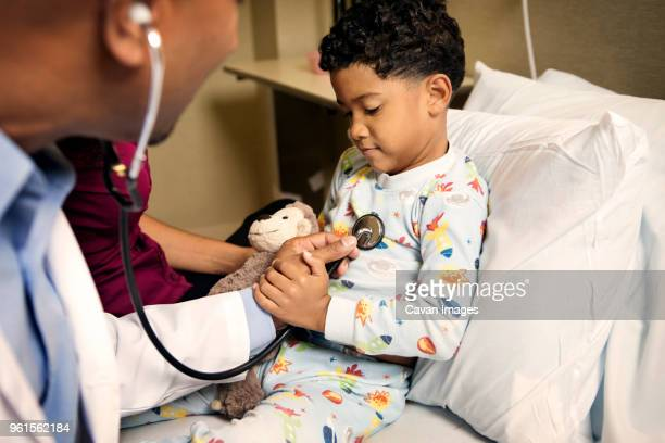 Doctor examining boy on bed in hospital