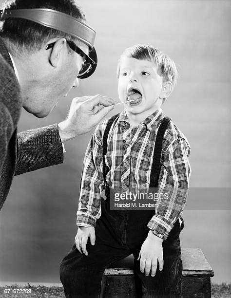 doctor examining boy - number of people stock pictures, royalty-free photos & images