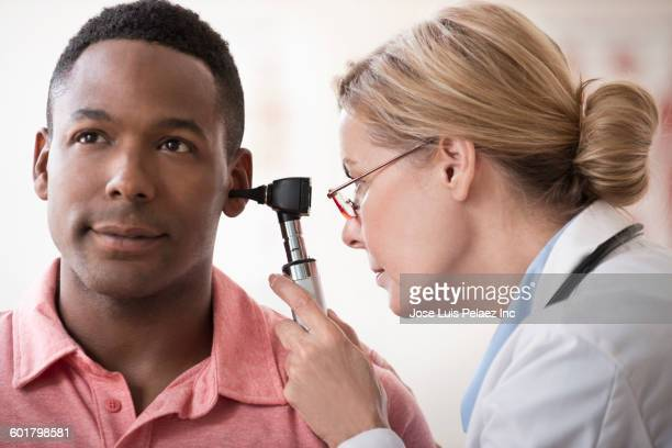 Doctor examining ear of patient in clinic