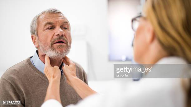 doctor examining external gland - tonsil stock photos and pictures