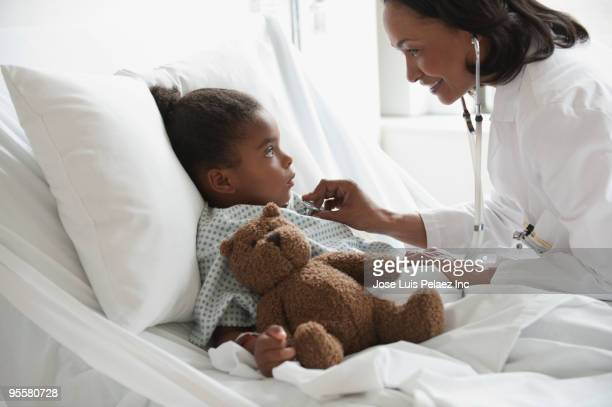doctor examining girl in hospital bed - girl in hospital bed sick stock photos and pictures