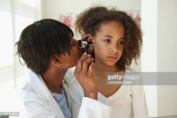 Doctor examining girl's ear with otoscope