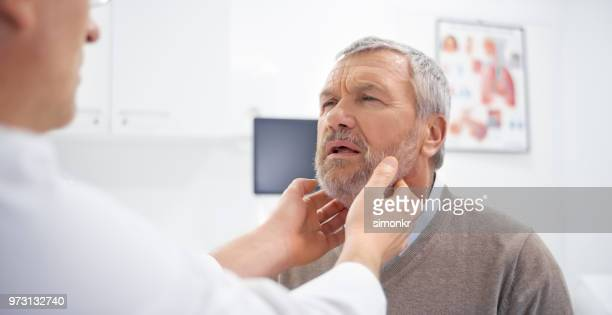 doctor examining glands - tonsil stock photos and pictures