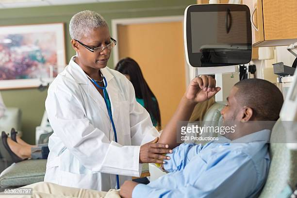 Doctor examining patient before he donates blood in hospital