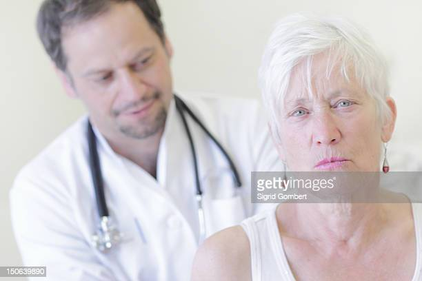 doctor examining patient in office - sigrid gombert stock pictures, royalty-free photos & images