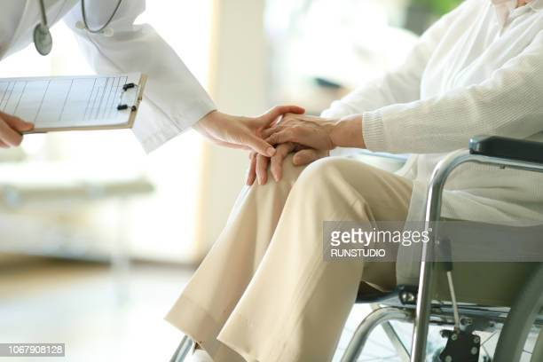doctor examining patient in wheelchair - nursing home stock pictures, royalty-free photos & images