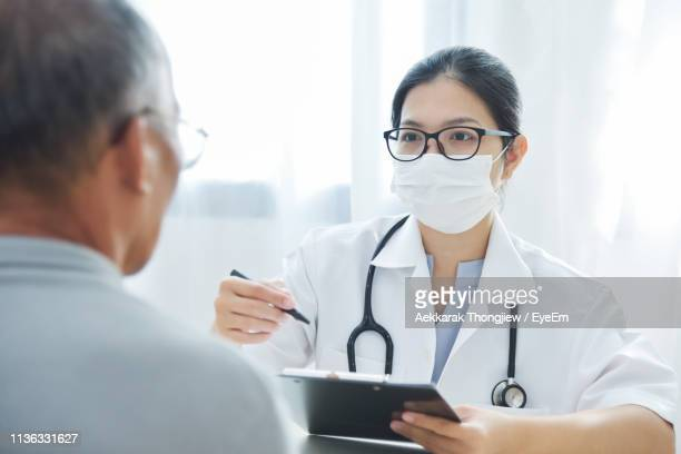 doctor examining patient - doctor mask stock pictures, royalty-free photos & images