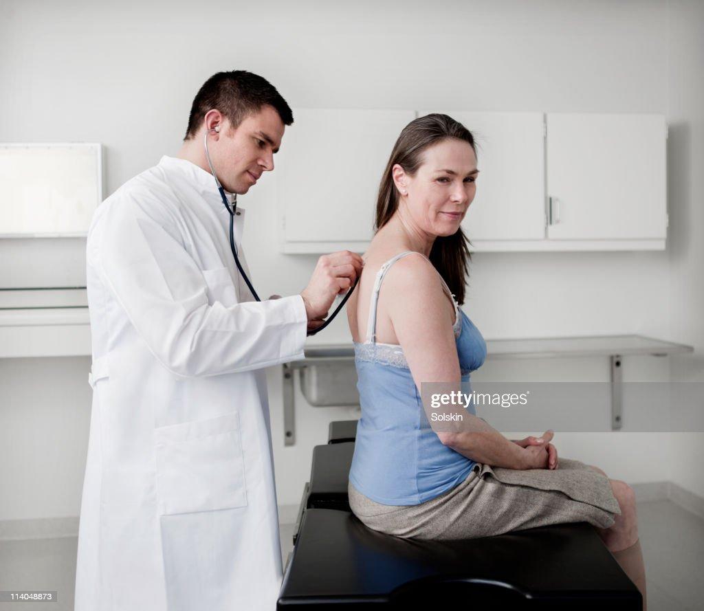 doctor examining patient : ストックフォト