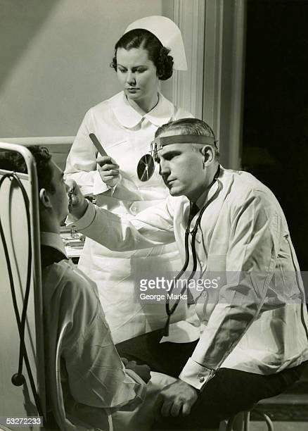 doctor examining patient - siglo xx fotografías e imágenes de stock