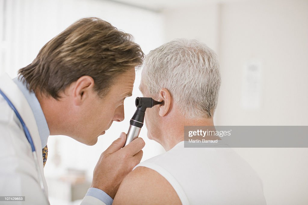 Doctor examining patients ear in doctors office : Stock Photo