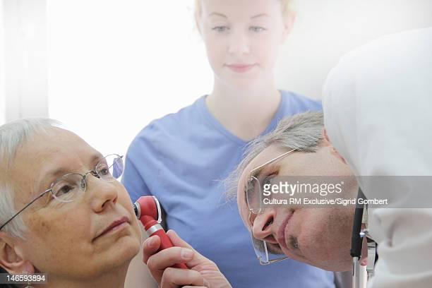 Doctor examining patients ear