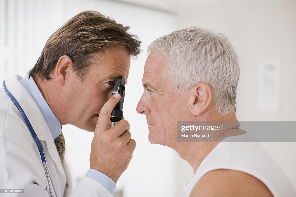 Doctor examining patients eye in doctors office : Stock Photo