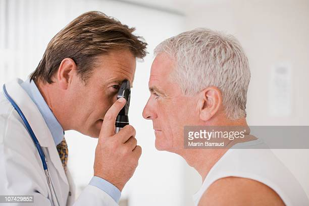 doctor examining patients eye in doctors office - eye test equipment stock pictures, royalty-free photos & images