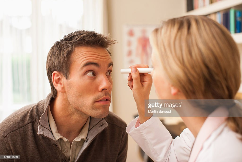 Doctor examining patient's eye in doctor's office : Stock Photo