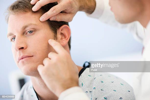 Doctor Examining Patient's Face