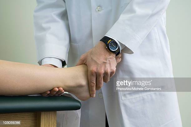 doctor examining patient's feet and ankle - ankle stock pictures, royalty-free photos & images