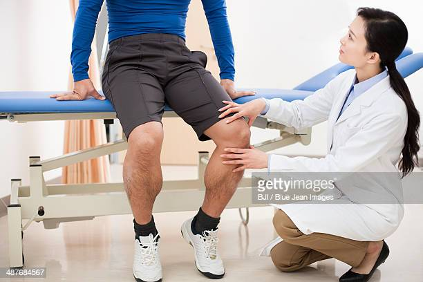 doctor examining patient's leg - knees together stock photos and pictures