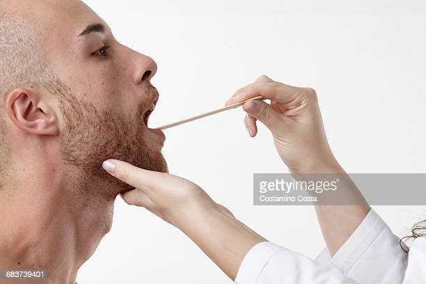 Doctor examining patients mouth with spatula
