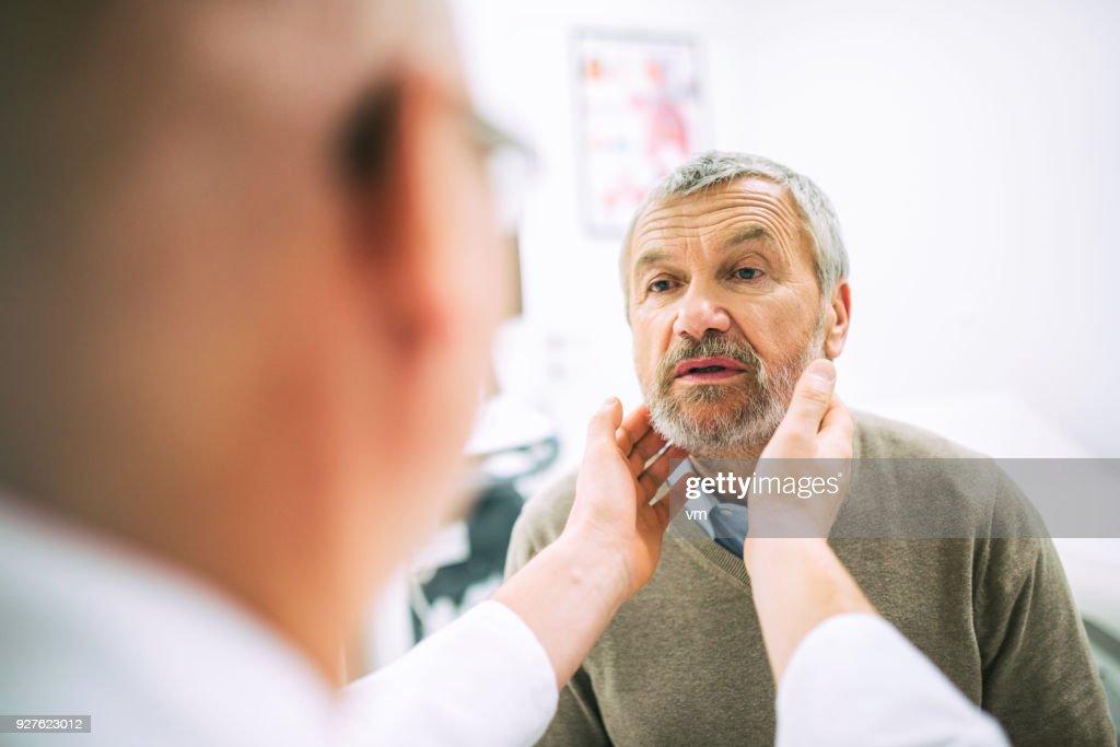 Doctor examining patient's throat : Stock Photo