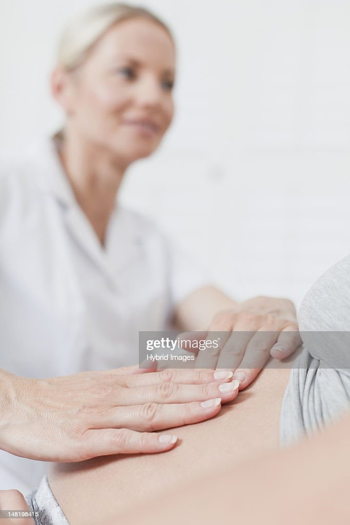Doctor examining pregnant womans belly : Stock Photo