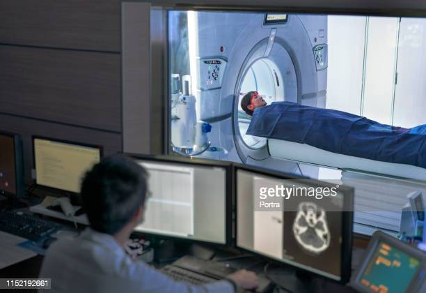 doctor examining scan while patient in mri scanner - mri scan stock pictures, royalty-free photos & images