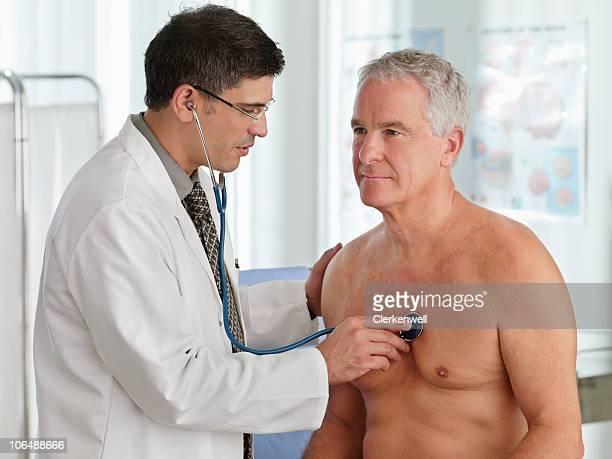 Doctor examining senior man with stethoscope