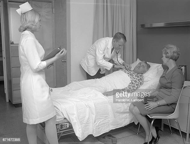 'Doctor Examining Senior Man, Women Standing Beside And Looking At Him'