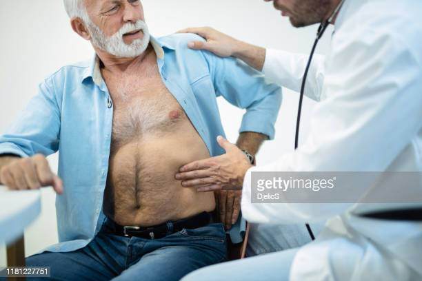 doctor examining senior man's painful stomach. - stomaco umano organo interno foto e immagini stock