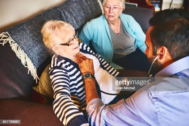 Doctor examining senior woman during home visit